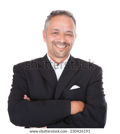 Portrait of smiling mature businessman standing arms crossed over white background - stock photo