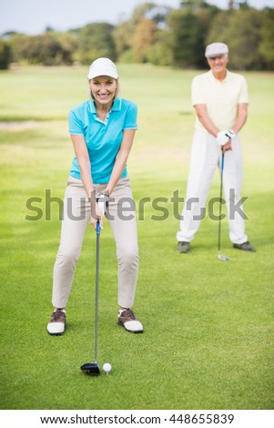 Portrait of smiling mature couple playing golf while standing on field