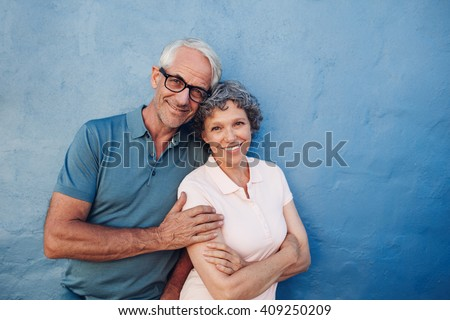 Portrait of smiling mature couple standing together against blue background. Happy middle aged man and woman against a wall. - stock photo