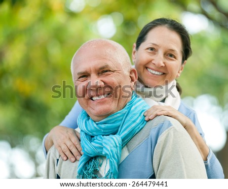 Portrait of smiling mature couple together in autumn park - stock photo