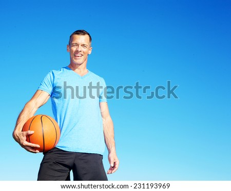 Portrait of smiling mature man holding basketball against clear blue sky - stock photo