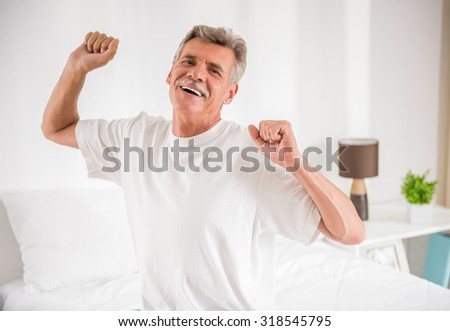 Portrait of smiling mature man is stretching his arms on bed. - stock photo