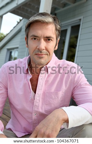 Portrait of smiling mature man with pink shirt - stock photo