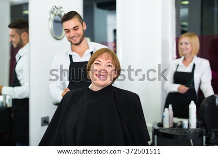 Portrait of smiling mature woman cutting hair in the barbershop