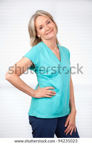 Portrait of smiling mature woman posing over white background - stock photo