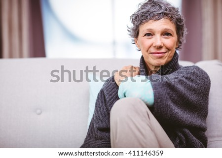 Portrait of smiling mature woman sitting on sofa at home - stock photo