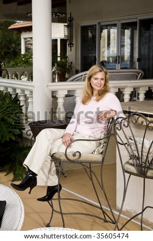Portrait of smiling mature woman sitting on wrought iron barstool on patio - stock photo