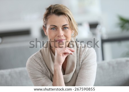 Portrait of smiling mature woman with hand on chin - stock photo