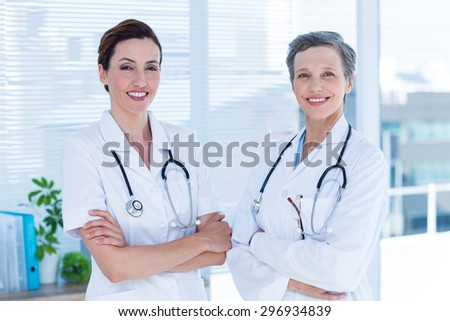 Portrait of smiling medical colleagues with arms crossed in the hospital - stock photo