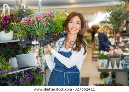 Portrait of smiling mid adult female florist carrying crate full of flower plants in shop - stock photo