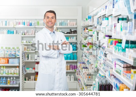 Portrait of smiling mid adult male pharmacist standing arms crossed in pharmacy - stock photo