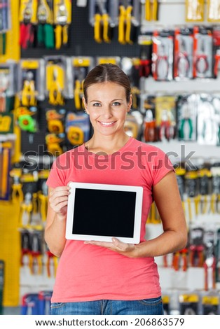 Portrait of smiling mid adult woman displaying digital tablet in hardware shop