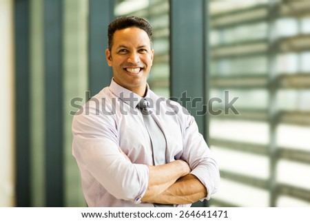portrait of smiling mid age businessman in office building - stock photo