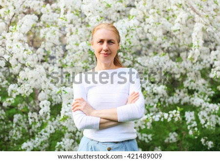 Portrait of smiling middle age woman in flowering spring garden - stock photo