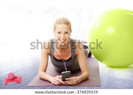 Portrait of smiling middle age woman lying on yoga mat after fitness workout next to exercise ball and listening music.
