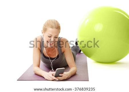 Portrait of smiling middle age woman lying on yoga mat and listening music after fitness workout. Isolated on white background.
