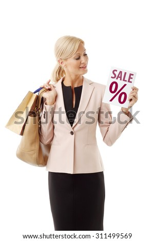 Portrait of smiling middle age woman standing against white background. Middle age female holding hand many shopping bags and sale sign. - stock photo