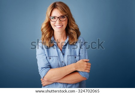 Portrait of smiling middle age woman wearing casual clothing while standing against isolated background and looking at camera.  - stock photo