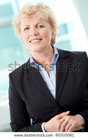 Portrait of smiling middle aged businesswoman looking at camera - stock photo