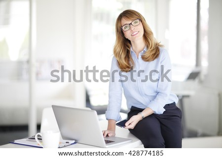 Portrait of smiling middle aged businesswoman using laptop and mobile while working at her workplace.