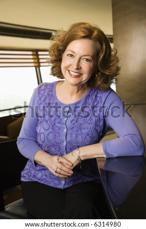 Portrait of smiling middle aged Caucasian woman sitting at otherwise empty bar. - stock photo