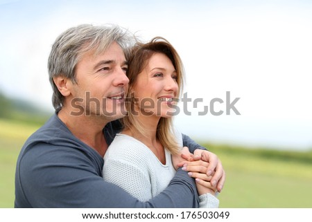Portrait of smiling middle-aged couple in countryside - stock photo