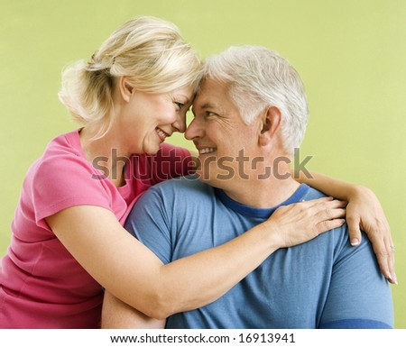 Portrait of smiling middle-aged couple in front of green wall snuggling. - stock photo