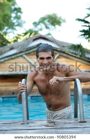 Portrait of smiling middle aged man standing in the pool - stock photo