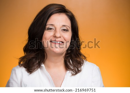 Portrait of smiling middle aged woman isolated on orange background. Positive human emotions, facial expressions, feelings, life perception, attitude  - stock photo