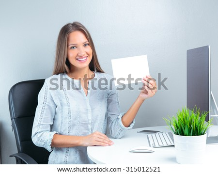 Portrait of smiling modern business woman in office holding blank paper  - stock photo