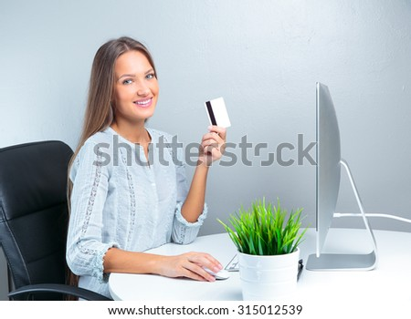 Portrait of smiling modern business woman in office using credit card for transactions - stock photo