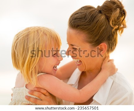 Portrait of smiling mother and baby girl hugging on beach at the evening - stock photo