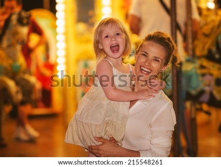 Portrait of smiling mother and baby girl in front of carousel - stock photo