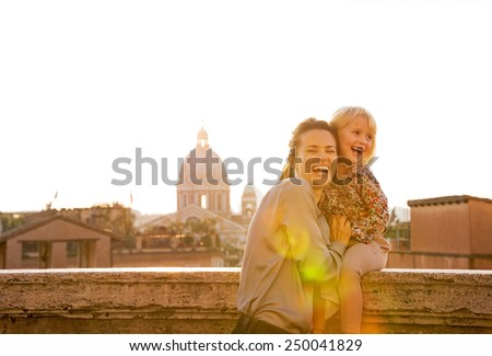Portrait of smiling mother and baby girl on street overlooking rooftops of rome on sunset