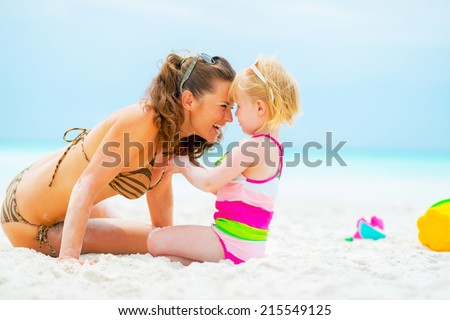 Portrait of smiling mother and baby girl playing on beach - stock photo