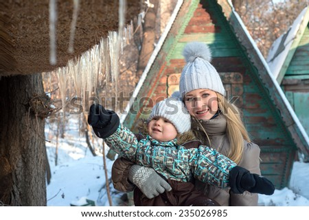 Portrait of smiling mother and baby in winter park, son hold icicle - stock photo