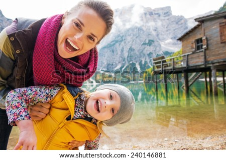 Portrait of smiling mother and baby on lake braies in south tyrol, italy - stock photo