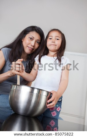 Portrait of smiling mother and cute little daughter in kitchen - stock photo