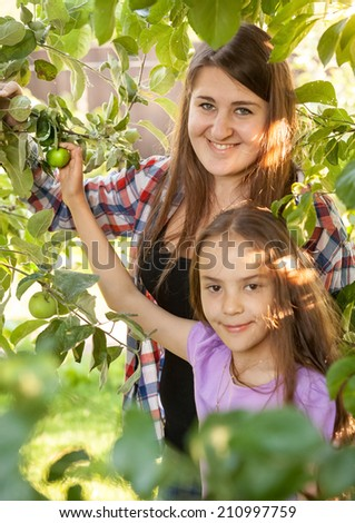 Portrait of smiling mother and daughter at apple garden