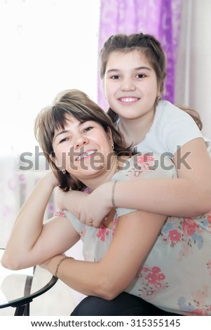 Portrait of smiling mother and daughter at home.  - stock photo