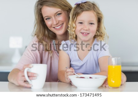 Portrait of smiling mother and daughter having breakfast at table - stock photo