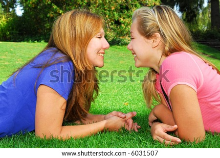 Portrait of smiling mother and daughter in summer park looking at each other - stock photo