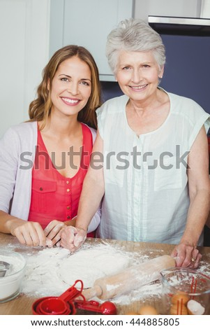 Portrait of smiling mother and daughter preparing food in kitchen at home - stock photo