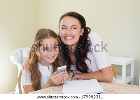 Portrait of smiling mother and holding mobile phone at table in house - stock photo