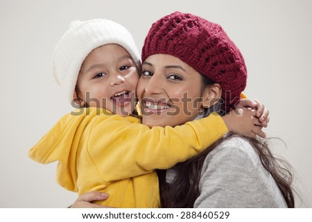 Portrait of smiling mother and son embracing - stock photo