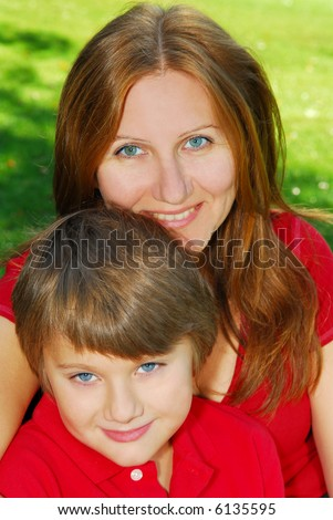 Portrait of smiling mother and son in summer park - stock photo