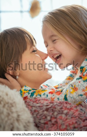 Portrait of smiling mother hugging her daughter lying and relax in the bed in a bright big white room - stock photo