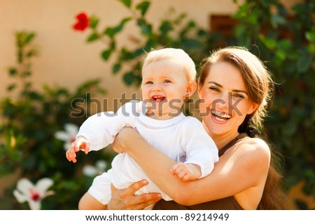 Portrait of smiling mother with baby on street - stock photo