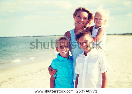 Portrait of smiling mother with children standing on the sunny beach. - stock photo