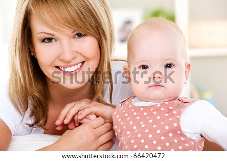 Portrait of  smiling mother with newborn baby at home - stock photo